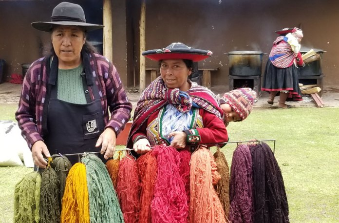 Nilda Callañaupa shows us what natural dye colors we will be producing. (Don't you love the baby sticking its head out from the manta?)