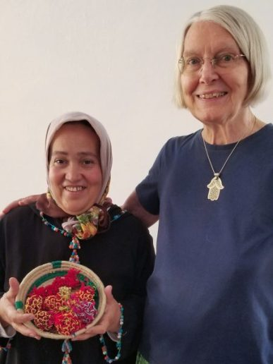 Amina Yabis poses (with a basket of buttons) next to her longtime friend Susan Schaefer Davis.
