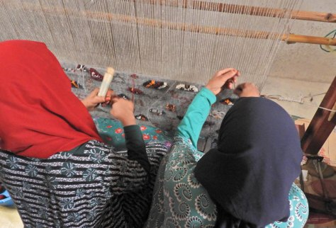 Fatima's daughters weaving side by side on a picture rug.