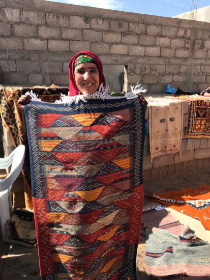 Fatima proudly displaying her rug.