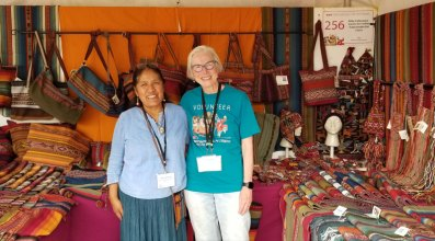 Nilda Callañaupa and Marilyn Murphy work together setting up CTTC booth at the International Folk Art Market in Santa Fe 2021.