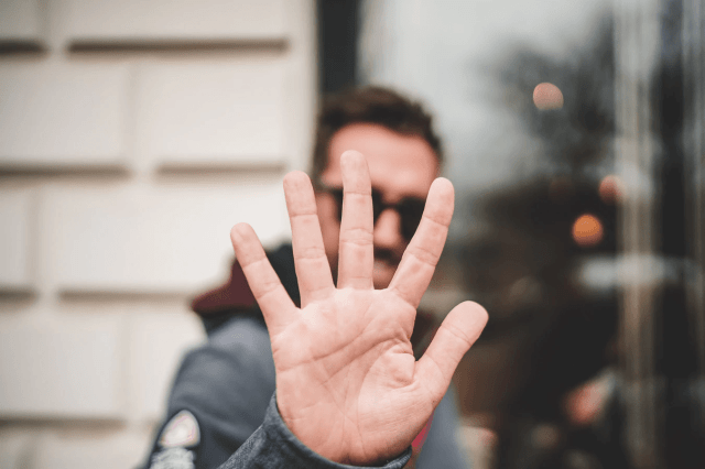 Man holding up five fingers in front of the camera.