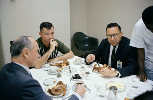 At breakfast before the flight, Young (center) has the face of a man with a sandwich in his spacesuit.