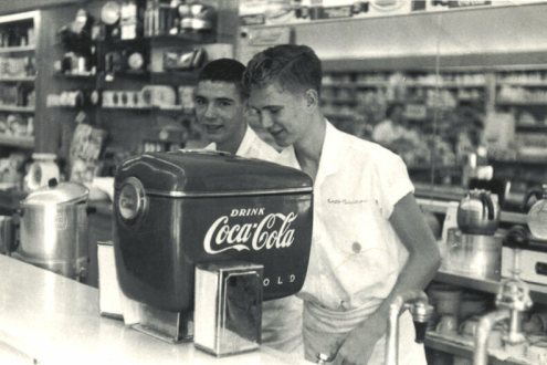 Two soda jerks serve Coca-Cola to customers.