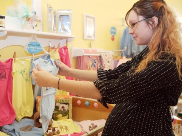 امرأة حامل ترفع ملابس طفل