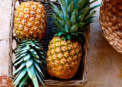 Two pineapples in wicker basket on table