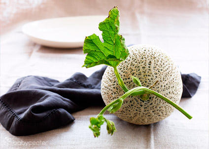Whole cantaloupe with green stem on table