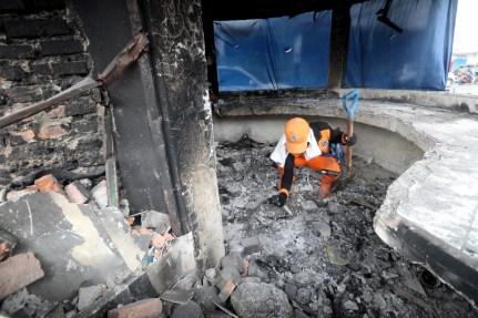 Pekerja membersihkan kesan kemusnahan di Jakarta akibat protes terhadap undang-undang cipta pekerjaan yang diperkenalkan oleh kerajaan Indonesia baru-baru ini. - Foto EPA