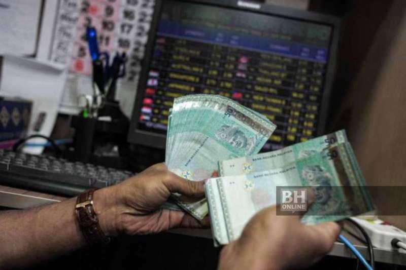Gambar fail: Pengurup wang sedang mengira not ringgit di Kuala Lumpur. - Foto AFP