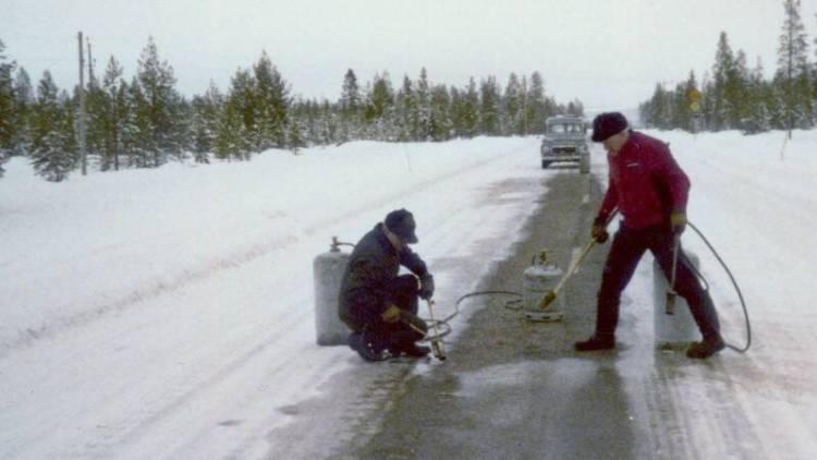 """Die """"Icemakers"""" Pelle Andersson (li.) und David Sundström (re.) präparieren eine Stelle der Landstraße N95 nahe Arjeplog für eine ABS-Erprobung mit rechten Rädern auf Eis und linken Rädern auf trockenem Untergrund, um 1975."""