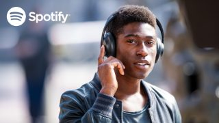 Spotify logo and man touching and holding the right earcup to listen to Spotify