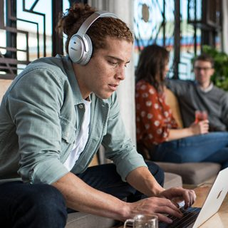 Person listening to music using QuietComfort 35 headphones