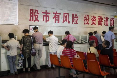 "Investors stand at trading terminals under a slogan ""The Stock Market has Risks, Use Caution When Investing"" at a securities exchange house in Shanghai, China, on Friday, Sept. 18, 2015. China's stocks headed for the steepest weekly loss this month in shrinking turnover amid growing concern government measures to support the world's second-largest equity market and economy are failing. Photographer: Qilai Shen/Bloomberg"