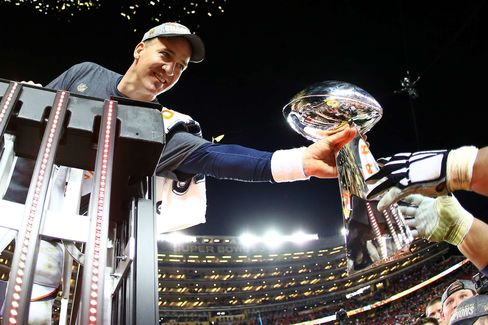 SANTA CLARA, CA - FEBRUARY 07:  Peyton Manning #18 of the Denver Broncos is handed the Vince Lombardi Trophy after defeating the Carolina Panthers during Super Bowl 50 at Levi's Stadium on February 7, 2016 in Santa Clara, California. The Broncos defeated the Panthers 24-10.  (Photo by Ronald Martinez/Getty Images)