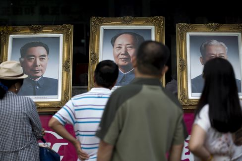 People look at portraits of former Chinese leaders Zhou Enlai, left, Mao Zedong, center, and Liu Shaoqi displayed in a shop on Wangfujing Street in Beijing, China, on Tuesday, Sept. 9, 2014.