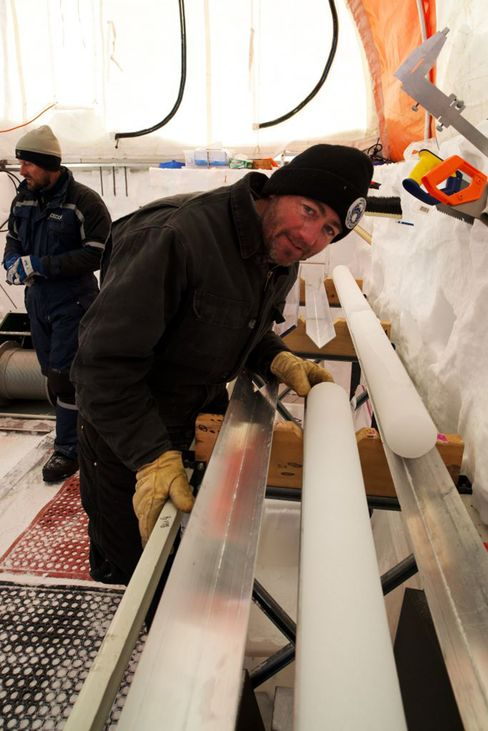 A glaciologist examines an ice core during the Aurora Basin North project in 2013.