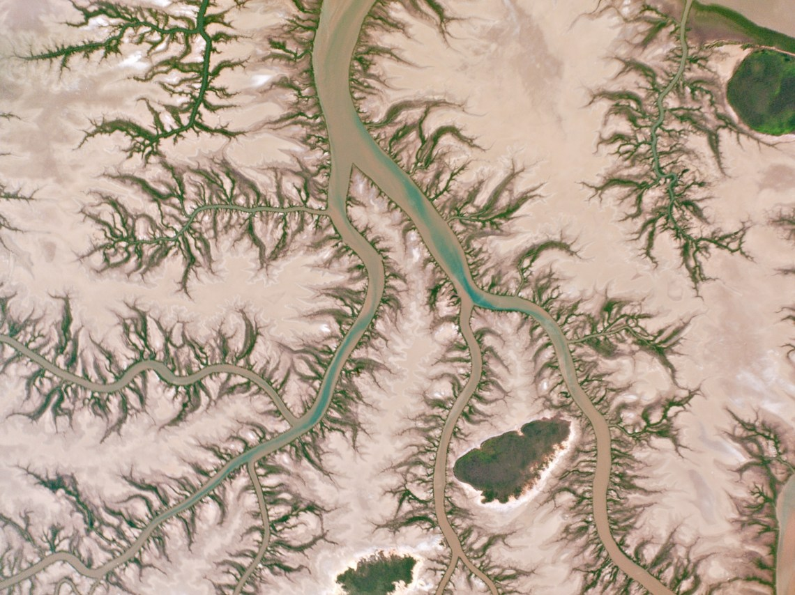 Branching streams lined with mangroves wind over tidal flats near Australia's remote Keep River Inlet.