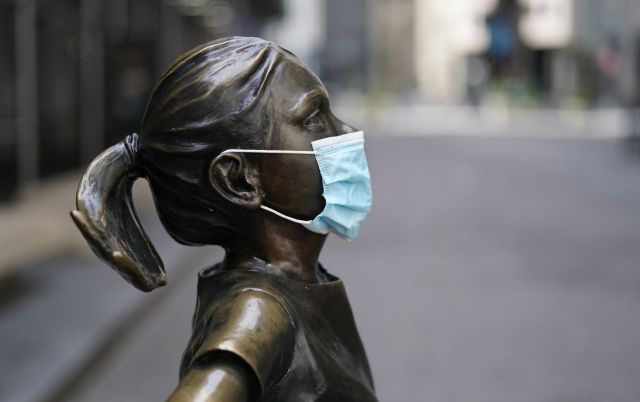 Fearless Girl, a bronze sculpture by Kristen Visbalthe, with a PPE mask on in front of the New York Stock Exchange in the Wall Street Financial District of Manhattan New York May 19, 2020.