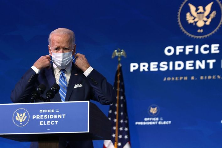 Joe Biden takes off his mask as he arrives at the Queen theater in Wilmington, Delaware on Jan. 14.