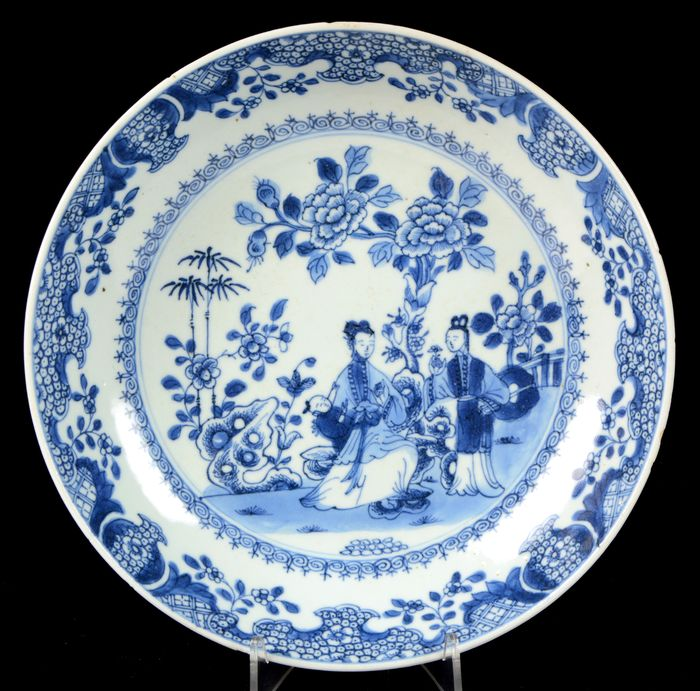 Plate - Blue and white - Porcelain - Pair of Chinese people, woman holding child, bamboo tree, peonias, rocks - China - Yongzheng (1723-1735)
