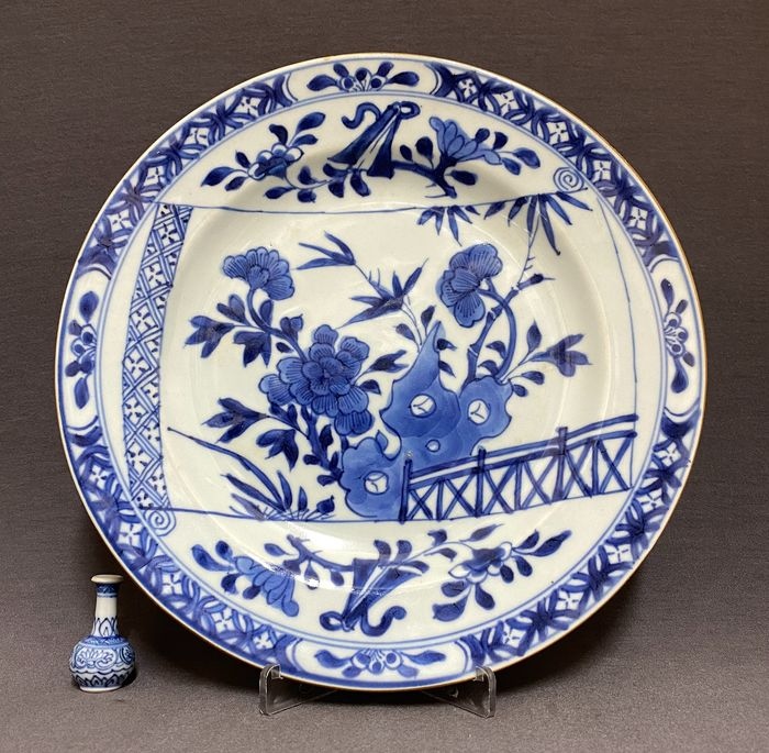 Plate - Porcelain - Chinese - Peonies, lilies, chrysanthemum and bamboo near pierced rock, behind fence on a scroll - China - Qianlong (1736-1795)