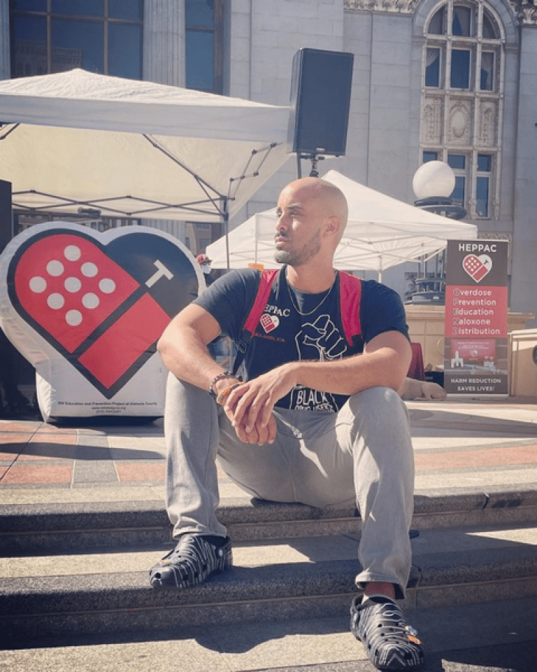 Braunz E. Courtney sits on the steps of Oakland's Oscar Grant Plaza on August 31—HEPPAC set up a booth to commemorate International Overdose Awareness Day, giving out free food and hosting Narcan trainings.