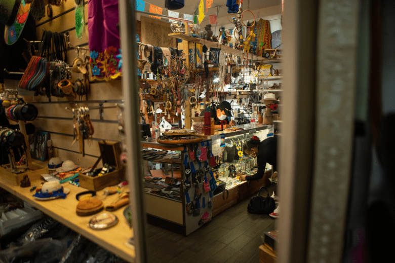 Mexican folk artist, [name] and wife Guadalupe inside of Adalynn's Fiesta Latina, their shop with handmade leather items and other goods.