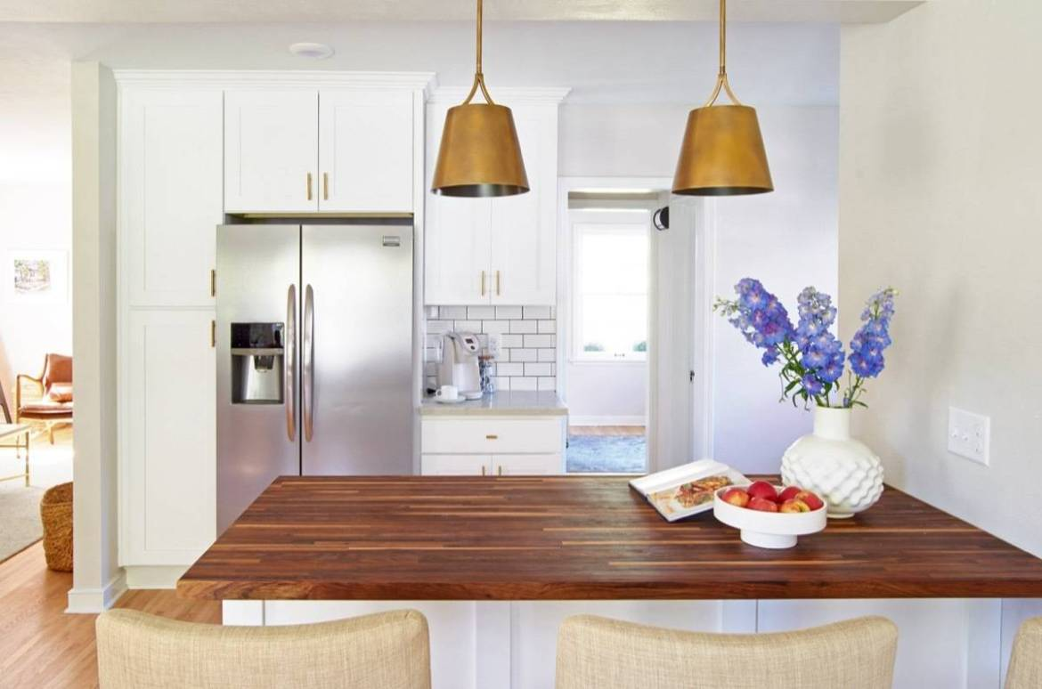 Curbly House kitchen, over butcher block island, white cabinets with gold hardware