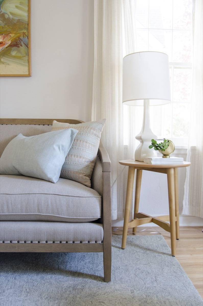 Nailhead trim sofa detail with side table and table lamp