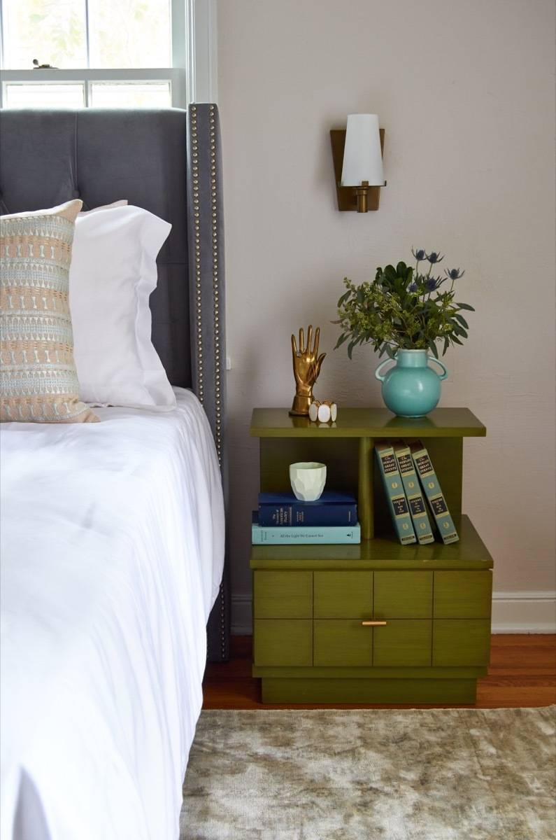 Green vintage bedside table with wall sconce
