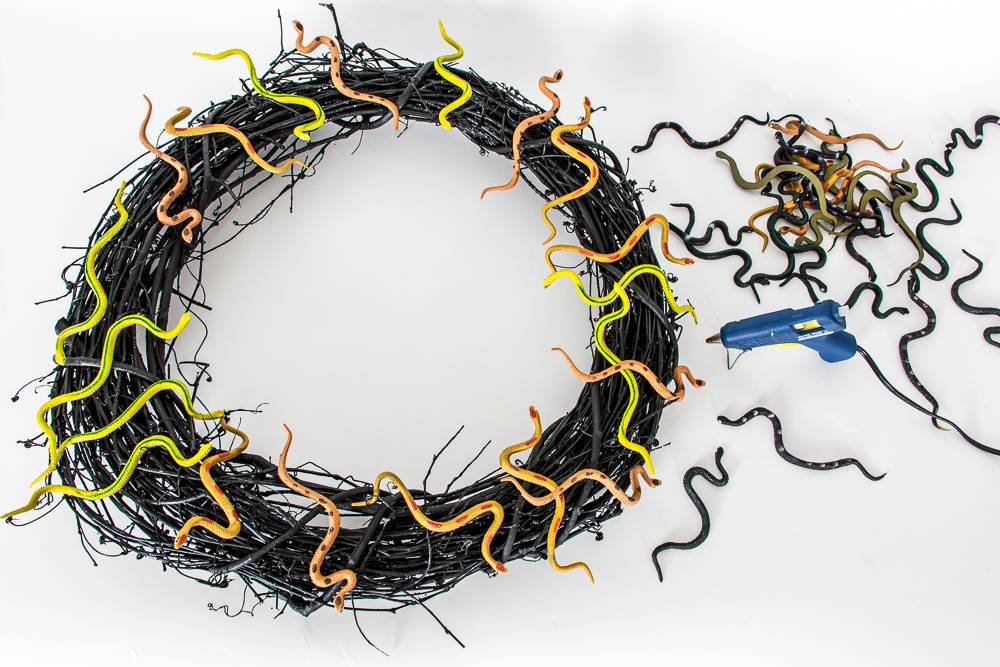 Glue the plastic snakes to the grapevine wreath
