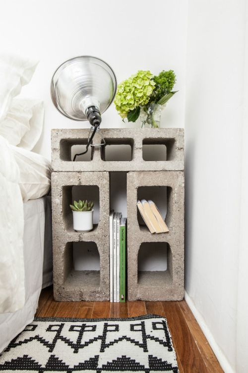 Cinder Blocks Bedside Table with Books and Plants White Bedding Black and White Rug Hardwood Flooring
