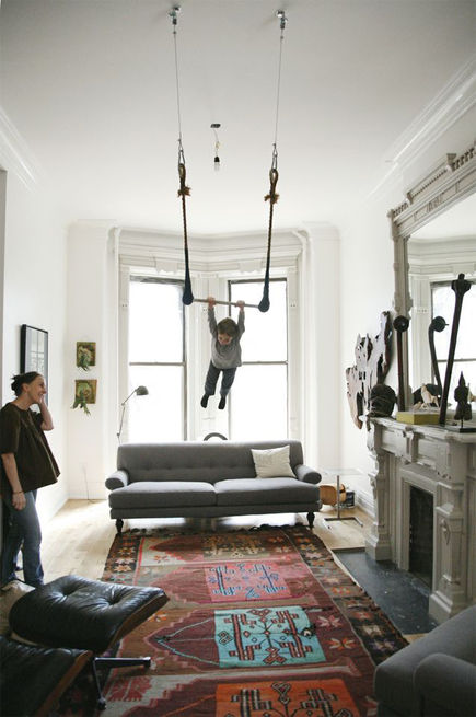 "A trapeze entertains the owners of this Brooklyn residence and their visitors. The trapeze ""was made by my teacher at circus school,"" says Sophie Demenge. ""I was living in San Francisco in a big Victorian house with roommates. The ceilings were so high I could hang the trapeze and practice at home. Now my kids are taking over—it's the first thing they do when they get up and the last before going to bed."""