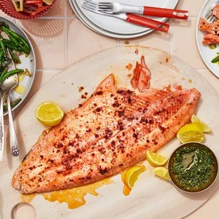 A whole side of salmon on a platter with a spicy sprinkle lemon wedges and an herby green sauce on the side for...