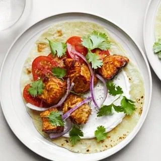 Photo of charred salmon with sour cream red onions tomatoes and cilantro on flour tortillas with two glasses of seltzer.
