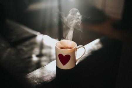 A hot mug of tea with a heart symbol on it.
