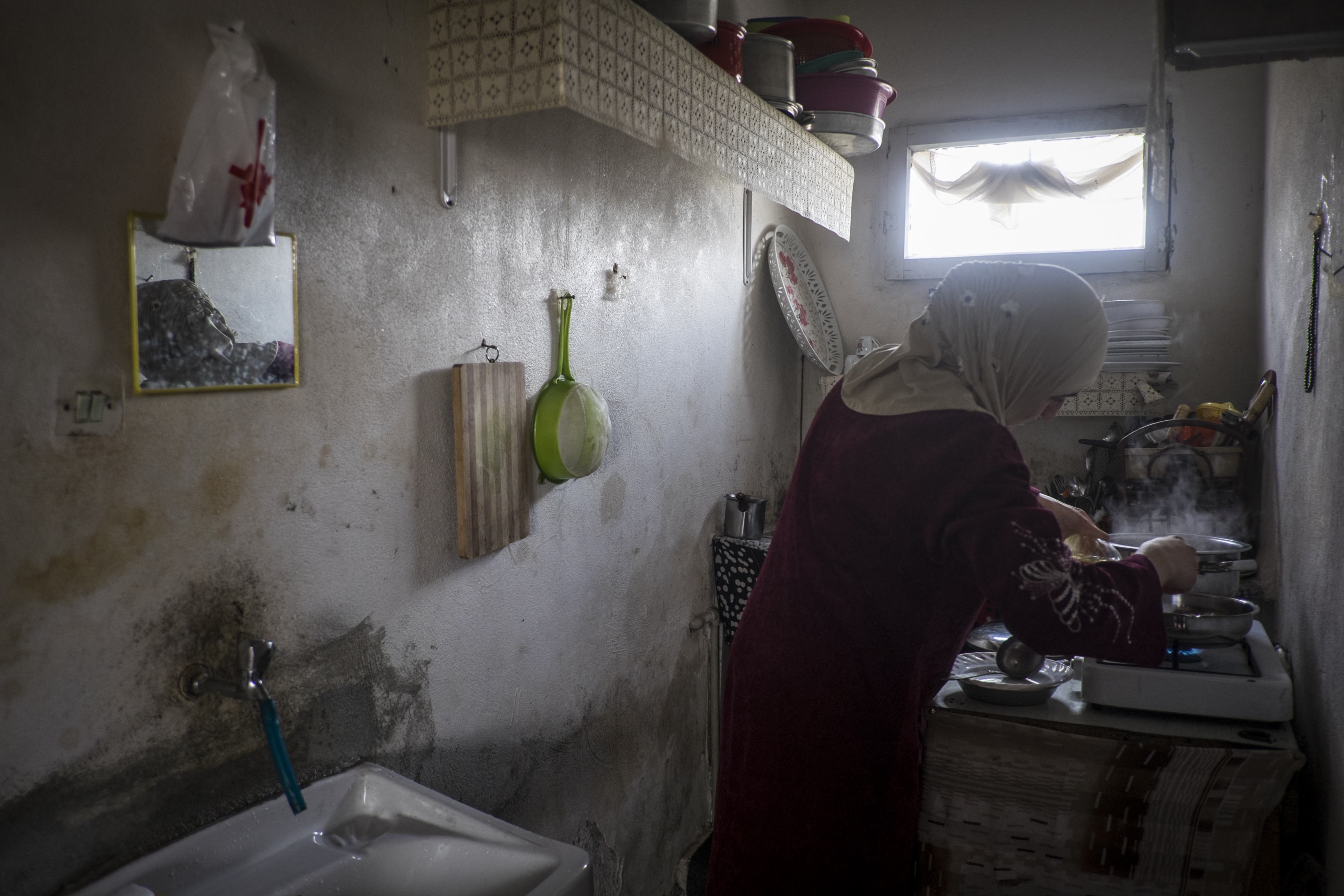 A woman cooks in a basement flat