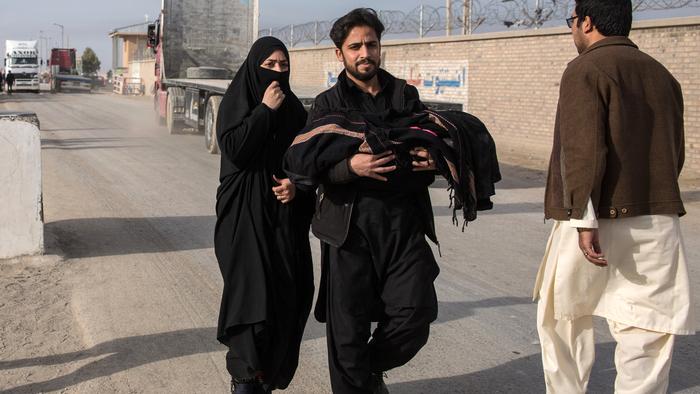 Afghan returnees walk across the Iranian border into Zaranj, Nimruz.