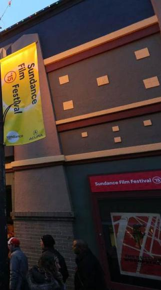 People stand in line at the Sundance Film Festival in front of the Egyptian Marquee building. A yellow Sundance Film Festival banner flies overhead.