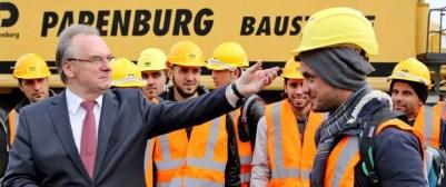 Der Ministerpräsident von Sachsen-Anhalt, Reiner Haseloff (CDU), mit syrischen Asylbewerbern, die sich für die Ausbildung zum Berufskraftfahrer interessieren Foto:  picture alliance / dpa