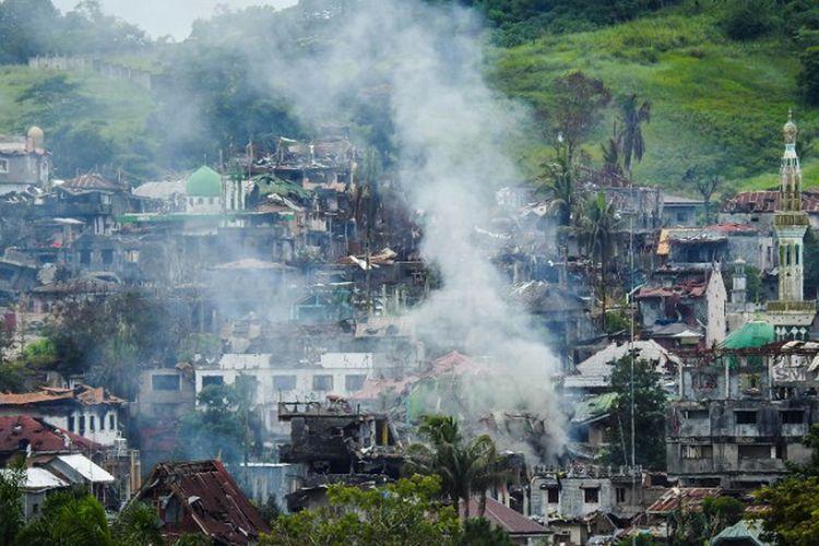 Asap mengudara dari bangunan-bangunan yang terbakar sebagai dampak dari pertempuran antara pasukan pemerintah Filipina dan gerombolan teroris di Kota Marawi. Pemandangan ini diabadikan pada 3 Juli 2017.