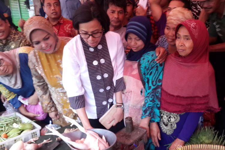 Menteri Keuangan RI Sri Mulyani Indrawati saat menimbang ayam potong di lapak salah satu pedagang di Pasar Besar Kota Malang, Kamis (4/1/2018).