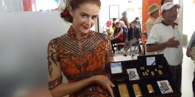 Seorang model saat menampilkan emas batangan dalam grand launching kerjasama antara PT Pos Indonesia dan PT Antam di Kantos Pos Malang, Senin (6/2/2017)