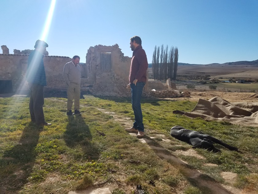 Alfonso and his father and brother standing near some of the ruins on their family land