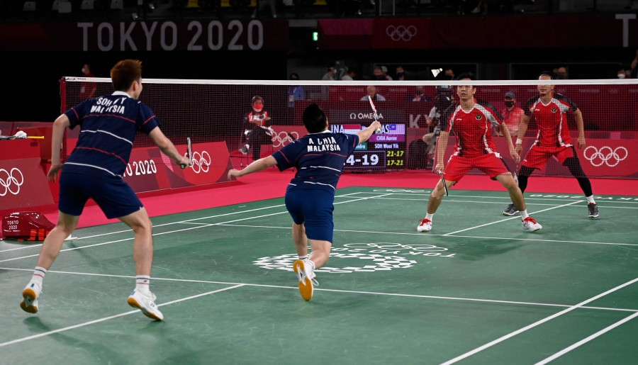 Malaysia's Soh Wooi Yik (C) hits a shot next to Aaron Chia in their men's doubles badminton bronze medal match against Indonesia's Mohammad Ahsan (R) and Indonesia's Hendra Setiawan during the Tokyo 2020 Olympic Games at the Musashino Forest Sports Plaza in Tokyo. - AFP Pic