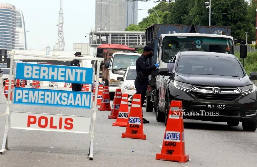 Police officers on duty during a roadblock at the Federal Highway today. -NSTP/HAIRUL ANUAR RAHIM