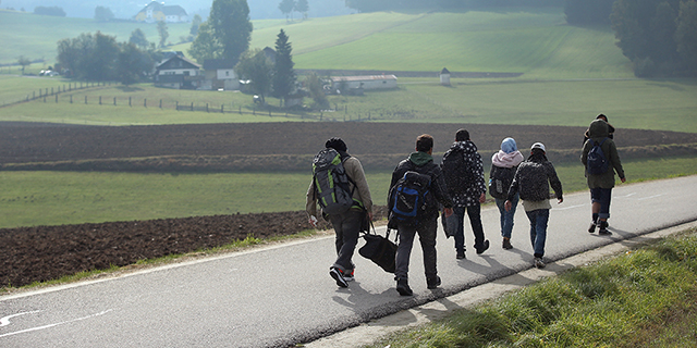 FUCHSOEDT, AUSTRIA - OCTOBER 17: Migrants who had arrived via buses chartered by Austrian authorities walk towards the border to Germany on October 17, 2015 near Fuchsoedt, Austria. According to a German police spokesman approximately 6,000 migrants are arriving daily over the Austrian border just in the area of southeastern Bavaria near the city of Passau. Most arrive via the Balkan route and once in Austria are transported by Austrian authorities to locations near the border to Germany. Germany has reportedly registered over 800,000 migrants this year, 400,000 in September alone. The migrants include many refugees from countries including Syria, Afghanistan and Iraq. Germany is struggling to accommodate the many migrants, most of whom will apply for asylum. (Photo by Sean Gallup/Getty Images)