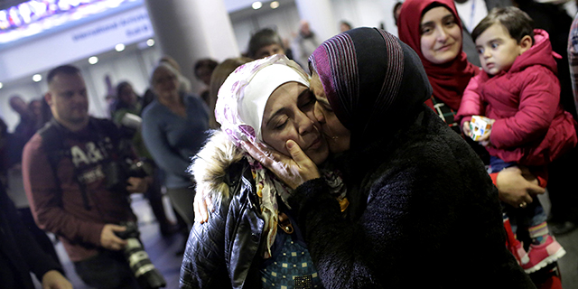 Syrian refugee Baraa Haj Khalaf receives a kiss from her mother, Fattoum Haj Khalaf, in February 2017 shortly after the family had arrived at Chicago's O'Hare International Airport. Her daughter Sham is held by her sister Aya at right. (Joshua Lott/AFP/Getty Images)