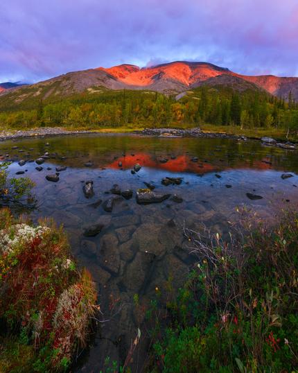 Красный блик на горе от восходящего солнца