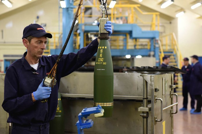 A man works on a shell casing in the BAE Systems factory.